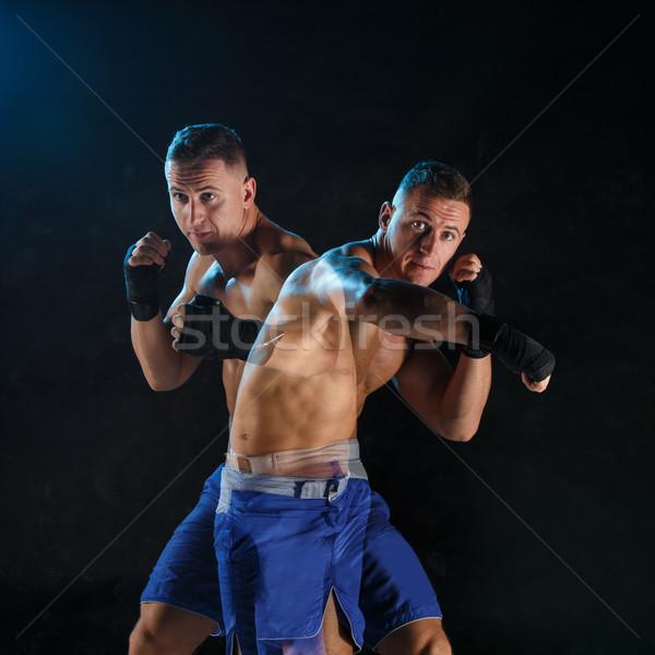 Stock photo: Male boxer boxing in a dark studio