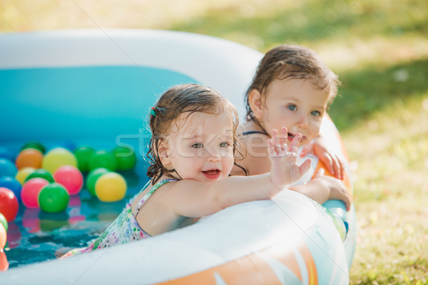 Stock photo: The two little baby girls playing with toys in inflatable pool in the summer sunny day
