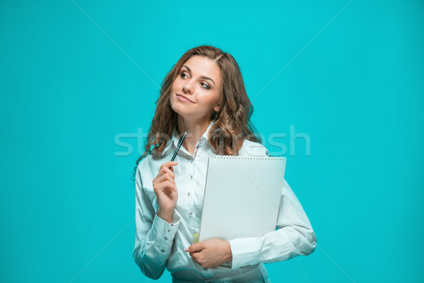 Stock photo: The smiling young business woman with pen and tablet for notes on blue background