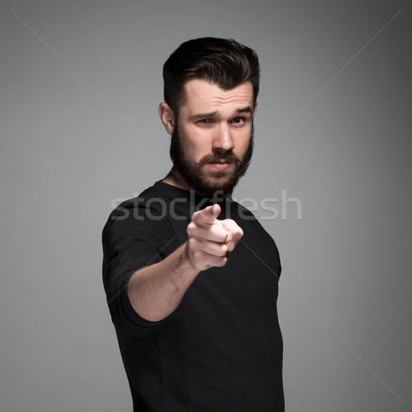 Young man with beard and mustaches, finger pointing towards the camera Stock photo © master1305