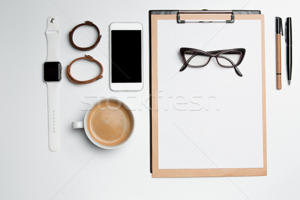 Stock photo: Office desk table with cup, supplies, phone on white