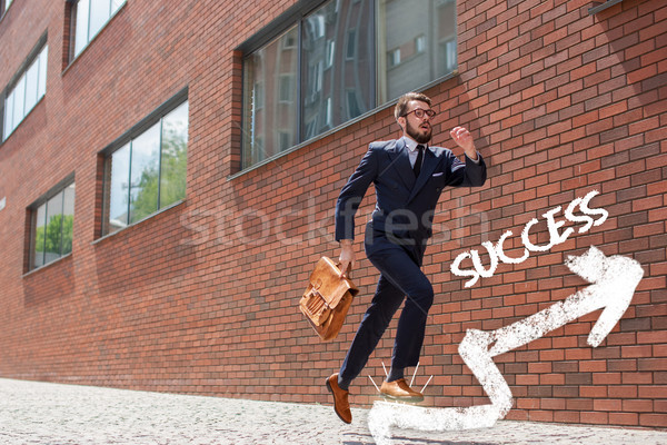 Stock photo: young businessman running in a city street