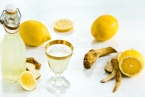 Stock photo: Home ginger tincture in a glass and fresh lemons on the white wooden background