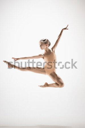 Young beautiful dancer in beige swimwear dancing on lilac background Stock photo © master1305