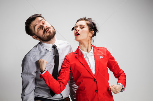 The angry business man and woman conflicting on a gray background Stock photo © master1305