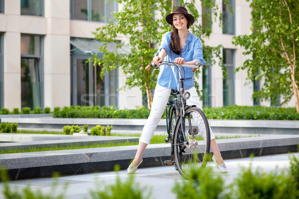 Pretty girl in hat riding a bicycle at street Stock photo © master1305