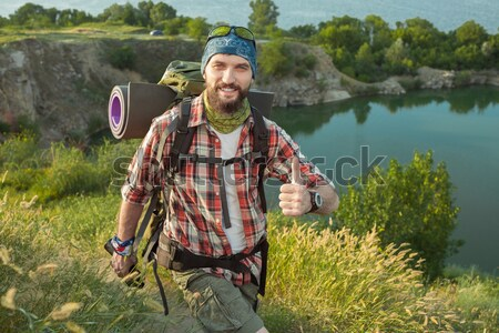 Young caucasian man with backpack sitting on the top of hill Stock photo © master1305