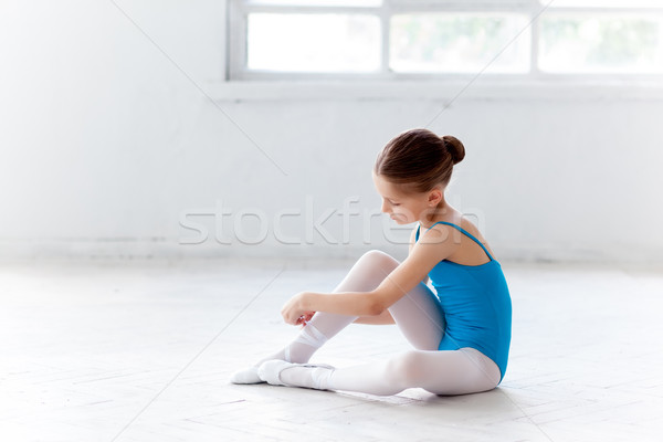 Beautiful little ballerina in blue dress for dancing puting on foot pointe shoes Stock photo © master1305
