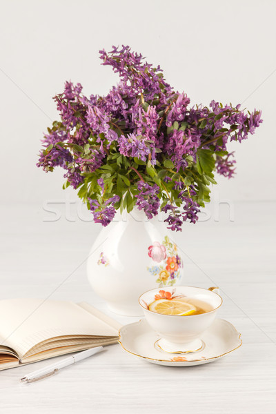Tea with  lemon and bouquet of  lilac primroses on the table Stock photo © master1305