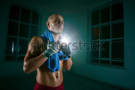 Male boxer boxing in punching bag with dramatic edgy lighting in a dark studio Stock photo © master1305