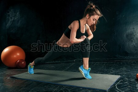 Beautiful slim brunette doing some stretching exercises in a gym Stock photo © master1305