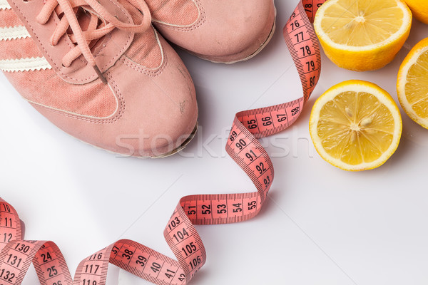 The old sneakers, a meter tape and lemon on an white Stock photo © master1305