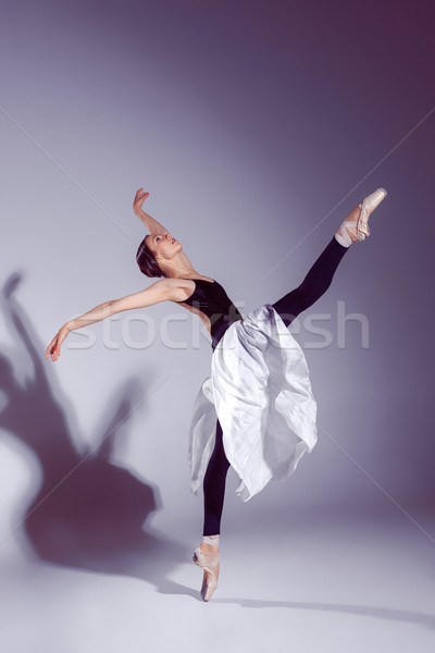 Ballerina in black outfit posing on toes, studio background. Stock photo © master1305