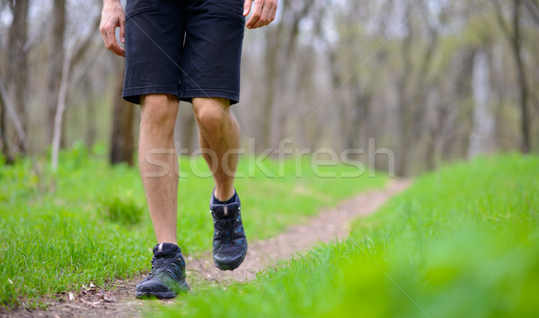 Stock photo: Close-up of Sportsman's Legs Walking on the Trail in the Wood. Active Lifestyle