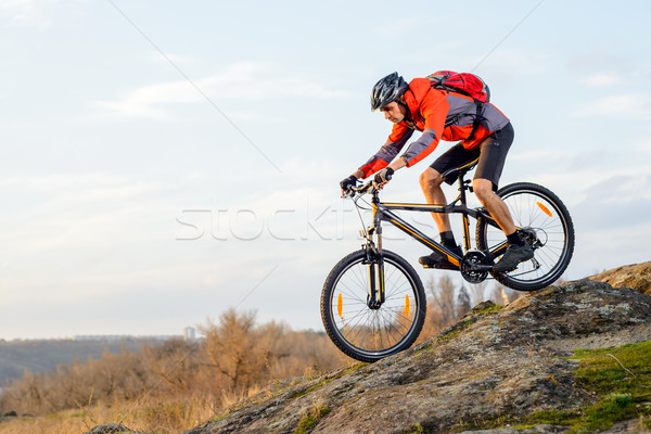 Cyclist in Red Jacket Riding the Bike Down Rocky Hill. Extreme Sport. Stock photo © maxpro