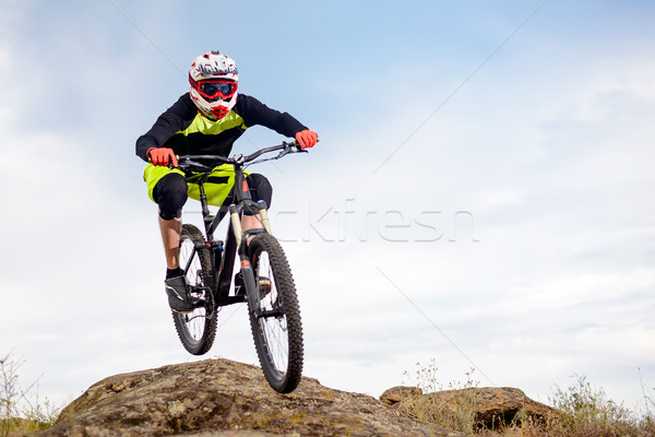 Professional Cyclist Jumping over Rock on the Mountain Bike on the Rocky Hill. Extreme Sport Concept Stock photo © maxpro