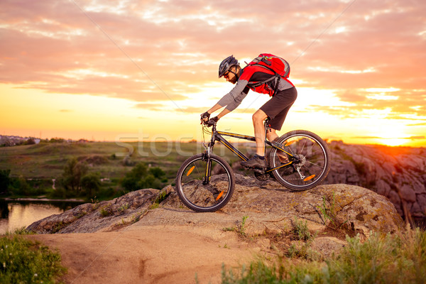 Stock photo: Cyclist Riding the Bike on the Mountain Rocky Trail at Sunset