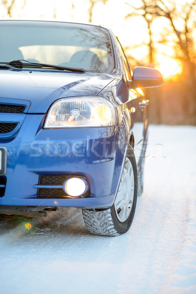 Blue Car with Winter Tires on Snowy Road at Sunset with Bright Sun. Travel and Safe Driving Concept. Stock photo © maxpro