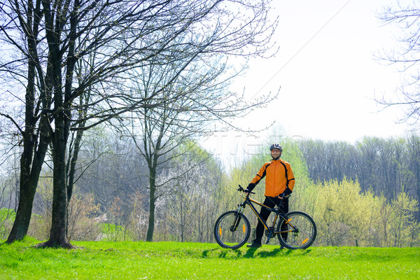 Cyclist with His Bike on the Green Meadow Stock photo © maxpro