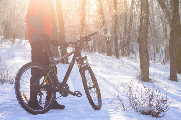 Stock photo: Mountain Biker with his Bike on the Snowy Trail in the Beautiful Winter Forest Lit by Sun