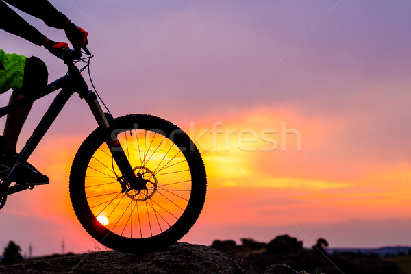 Stock photo: Professional Cyclist Resting with Down Hill Bike on the Rock at Sunset.