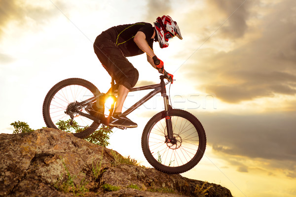 Stock photo: Professional Cyclist Riding the Bike Down Rocky Hill at Sunset. Extreme Sport.