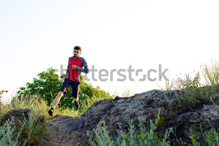 Young Sportsman Running on the Rocky Mountain Trai in the Evening. Active Lifestyle Stock photo © maxpro