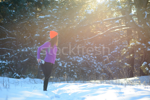 Young Woman Runner Stretching her Legs in Beautiful Winter Forest at Sunny Frosty Day. Active Lifest Stock photo © maxpro