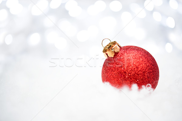 Stock photo: Christmas Decoration with Red Ball in the Snow on the Blurred Background with Holiday Lights. Greeti