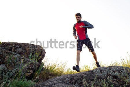 Stock photo: Young Sportsman Running on the Rocky Mountain Trai in the Evening. Active Lifestyle