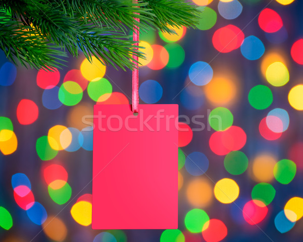 Christmas Greeting Card on the Fir Branch on the Holiday Lights Background Stock photo © maxpro