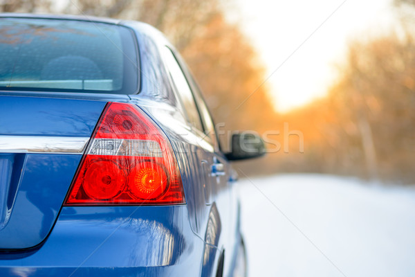 Stock photo: Blue Car on the Winter Snowy Road at Sunset. Close up Rear View. Travel and Drive Safe Concept.