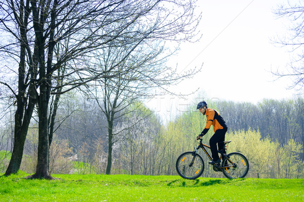 Stock photo: Cyclist Riding the Bike on the Green Meadow