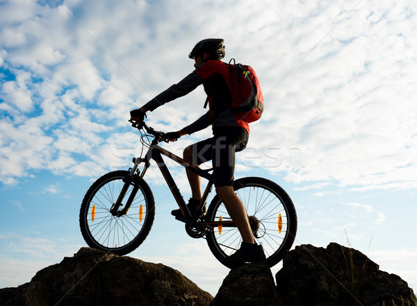 Stock photo: Silhouette of Cyclist with Bike on the Rock at Sunset. Extreme Sports.