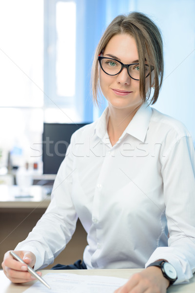 Stock photo: Young Attractive Smiling Businesswoman in White Signing the Document in Bright Modern Office