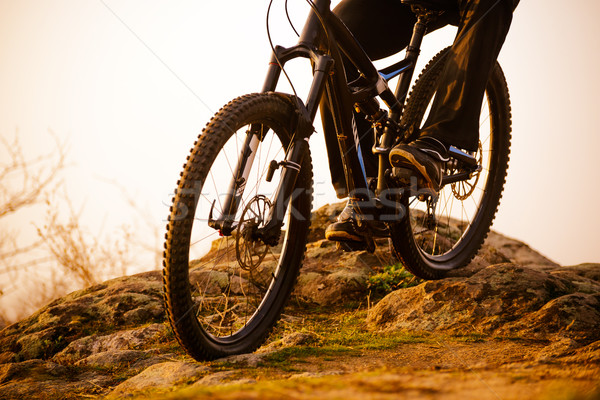 Enduro Cyclist Riding the Bike Down Rocky Hill at Sunset. Close up Extreme Sport Concept. Space for  Stock photo © maxpro