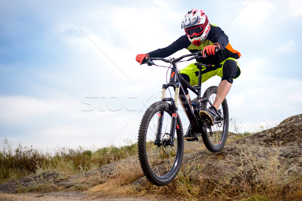 Professional Cyclist Riding the Bike Down Rocky Hill. Extreme Sport. Space for Text. Stock photo © maxpro
