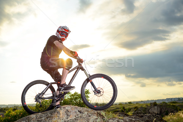 Professional Down Hill Cyclist Resting with Bike on the Rock at Sunset. Extreme Sport. Stock photo © maxpro