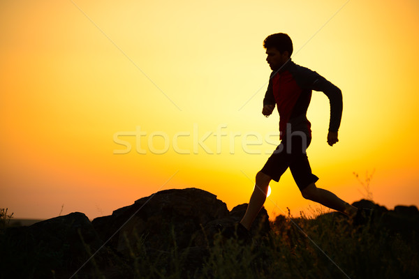 Young Sportsman Running on the Rocky Mountain Trail at Sunset. Active Lifestyle Stock photo © maxpro