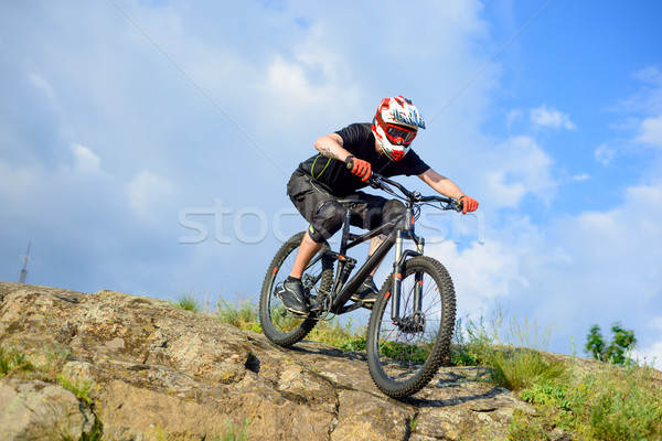 Stock photo: Professional Cyclist Riding the Bike Down Rocky Hill. Extreme Sport.