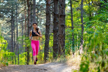 Young Woman Running on the Trail in the Beautiful Wild Pine Forest. Active Lifestyle Concept. Space  Stock photo © maxpro