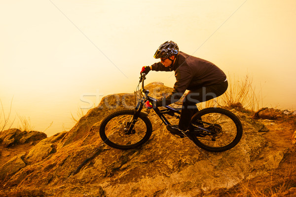 Stock photo: Enduro Cyclist Riding the Mountain Bike on the Rock. Extreme Sport Concept. Space for Text.