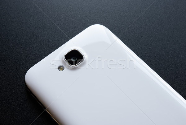 Stock photo: Close Up Image of the Camera of White Smart Phone on the Black Table