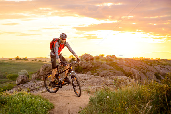 Stock photo: Cyclist Riding the Bike on Mountain Rocky Trail at Sunset