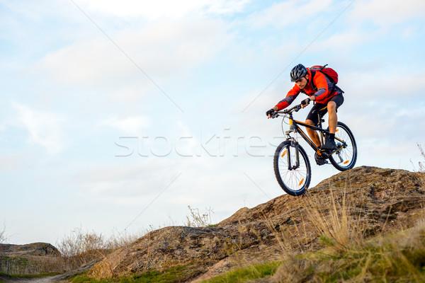 Kerékpáros piros kabát lovaglás bicikli lefelé Stock fotó © maxpro