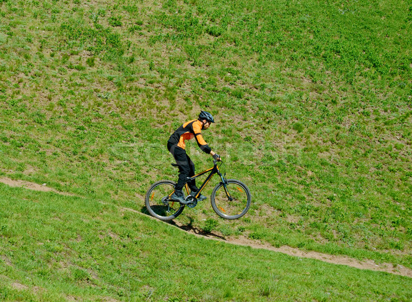 Cyclist Riding Down Hill on the Rear Wheel Stock photo © maxpro