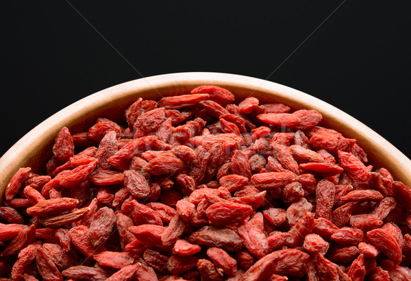 Stock photo: Wooden Bowl Full of Dried Goji Berries on the Black Table
