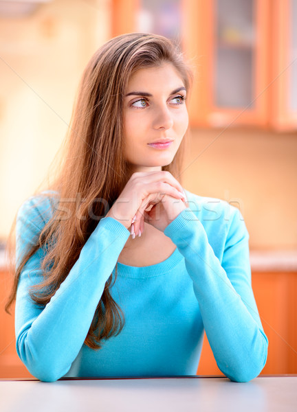 Portrait of a beautiful young lady sitting in the kitchen at home Stock photo © maxpro