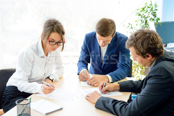 Stock photo: Business People Signing the Contract around the Table in Modern Office. Business Cooperation Concept