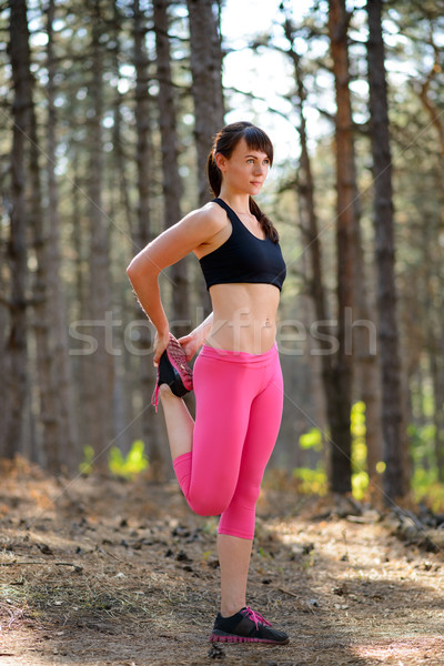 Stock photo: Young Fitness Woman Stretching her Legs in the Pine Forest. Female Runner Doing Stretches . Healthy